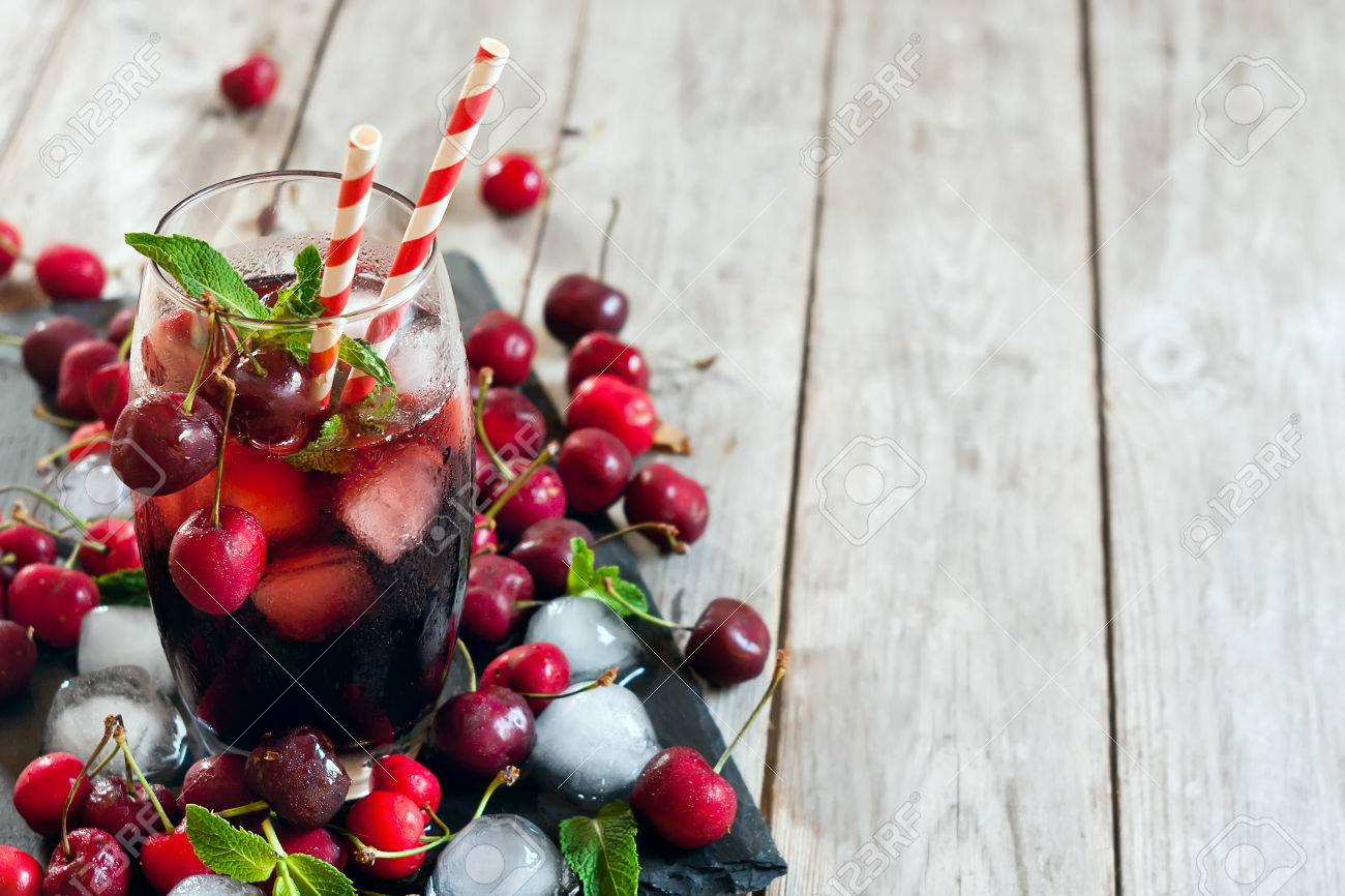 Cherry juice with ice cubes, mint leaves and ripe sweet cherry. Copy space background. - 41255919