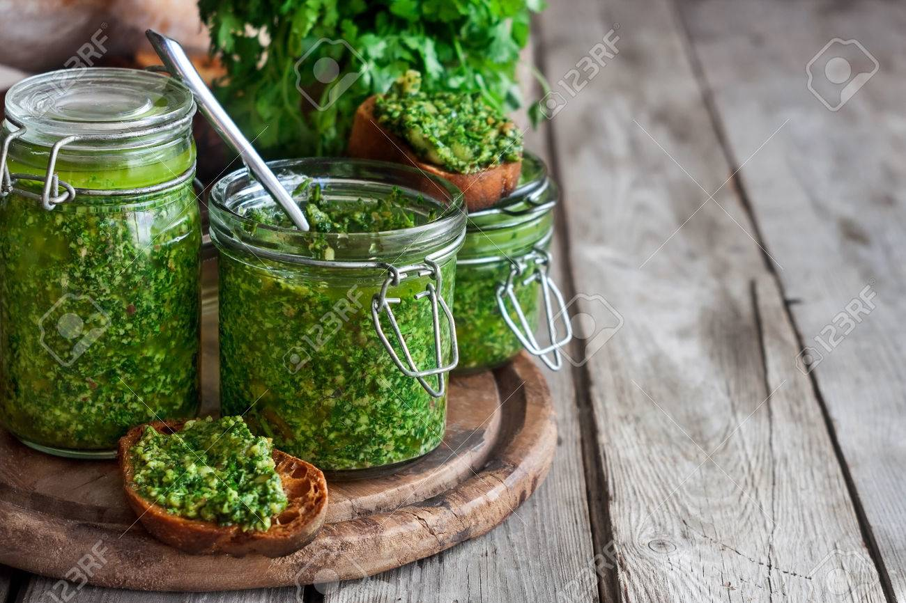 Homemade cilantro pesto in jars on wooden background - 51130155