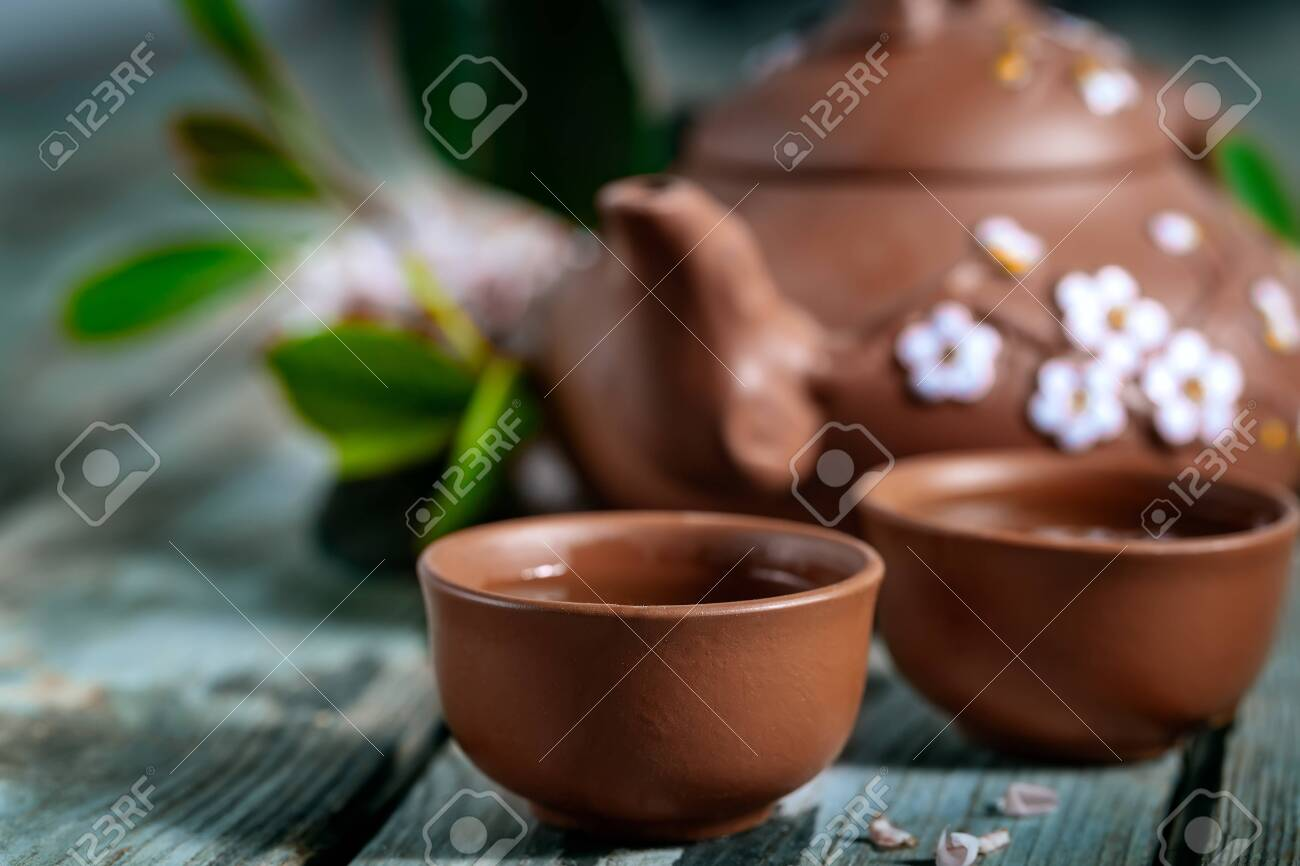 Tea in small brown yixing teapot and spring blossom on old wooden background. Selective focus. - 138663945