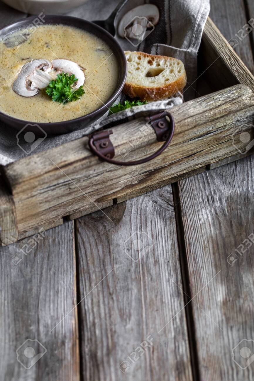 Delicious homemade mushrooum soup puree with portobello and wild mushrooms on rustic table. Copyspace background. - 140523092