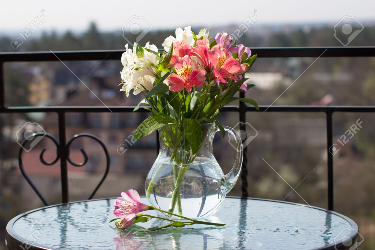 Spring Flower Bouquet In Glass Jug On Glass Table Stock Photo ...