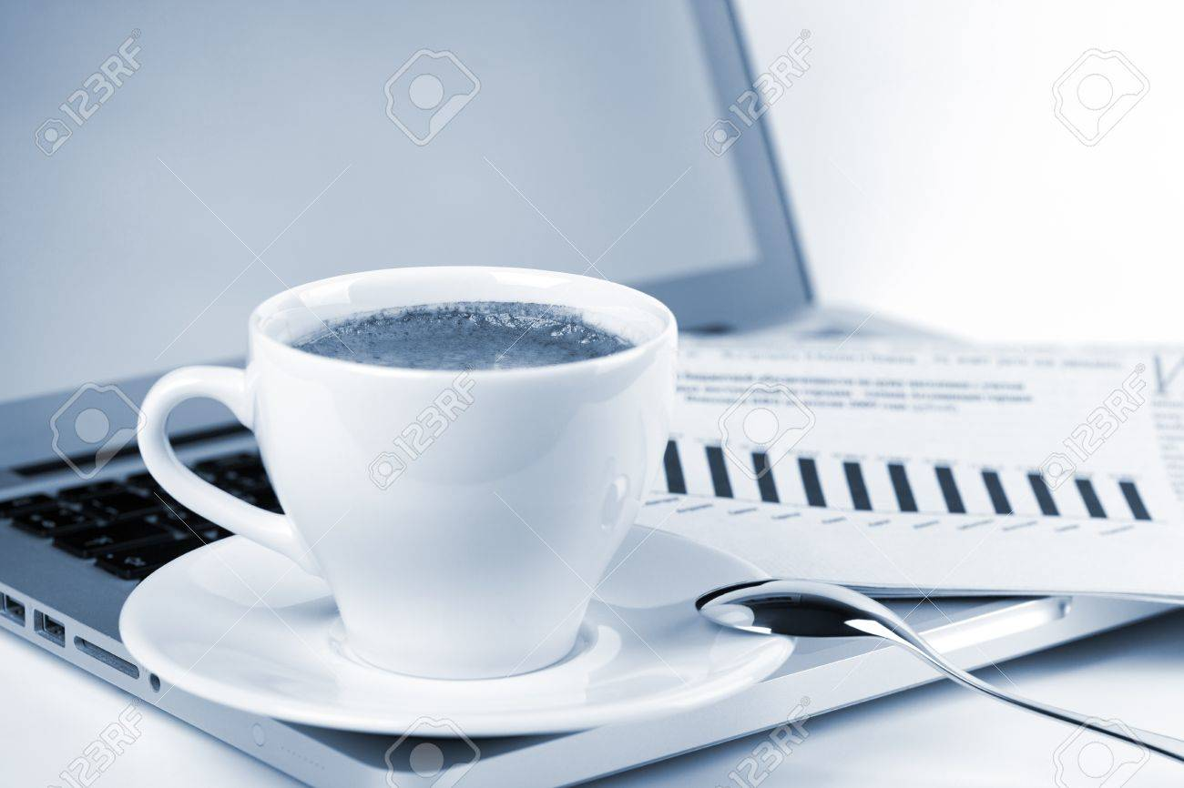 Cappuccino cup with laptop and newspaper. Blue toned Stock Photo - 8602616