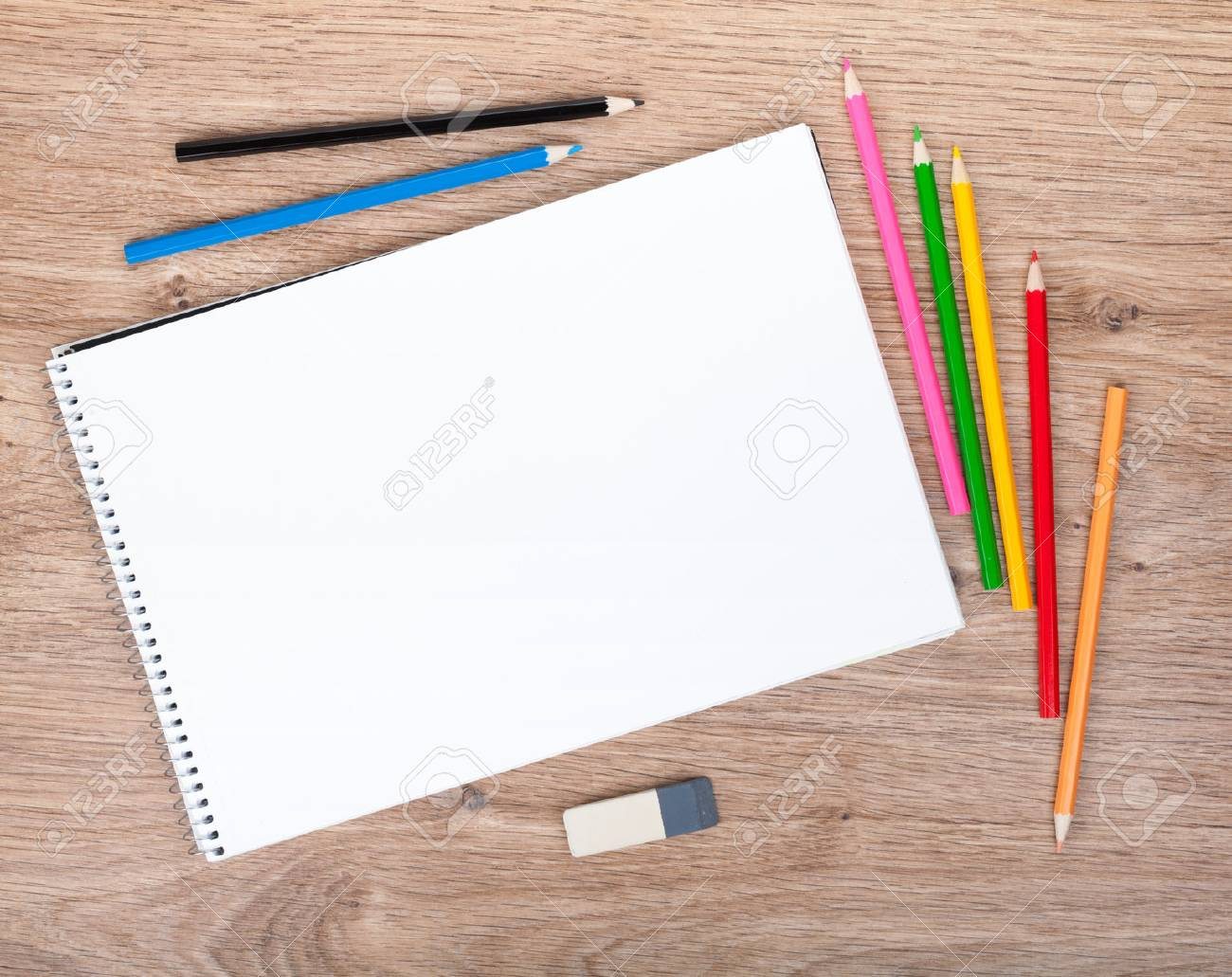 Blank paper and colorful pencils on the wooden table. View from above Stock Photo - 23319502