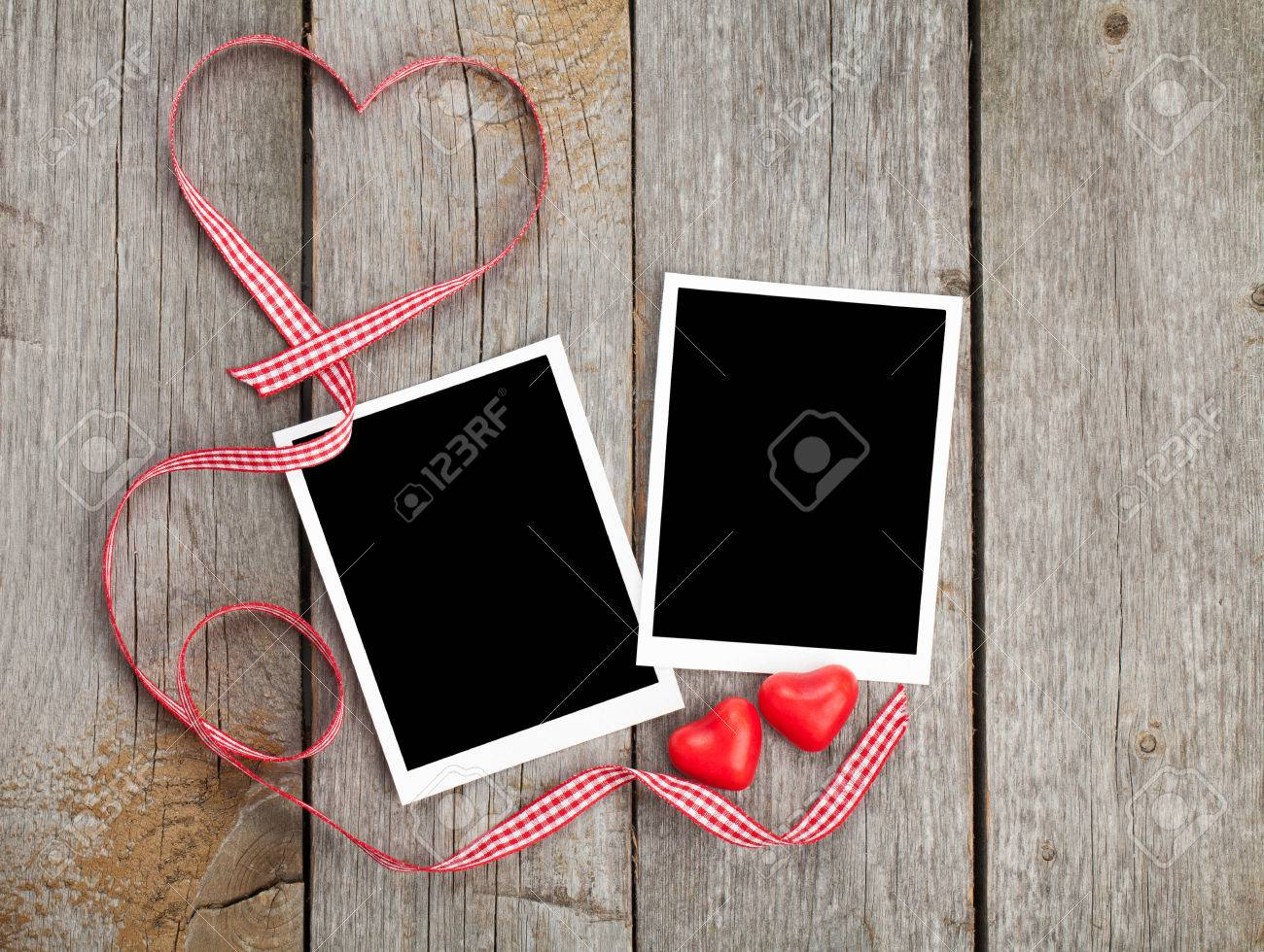 Two photo frames and small red candy heart on wooden background Stock Photo - 24951758