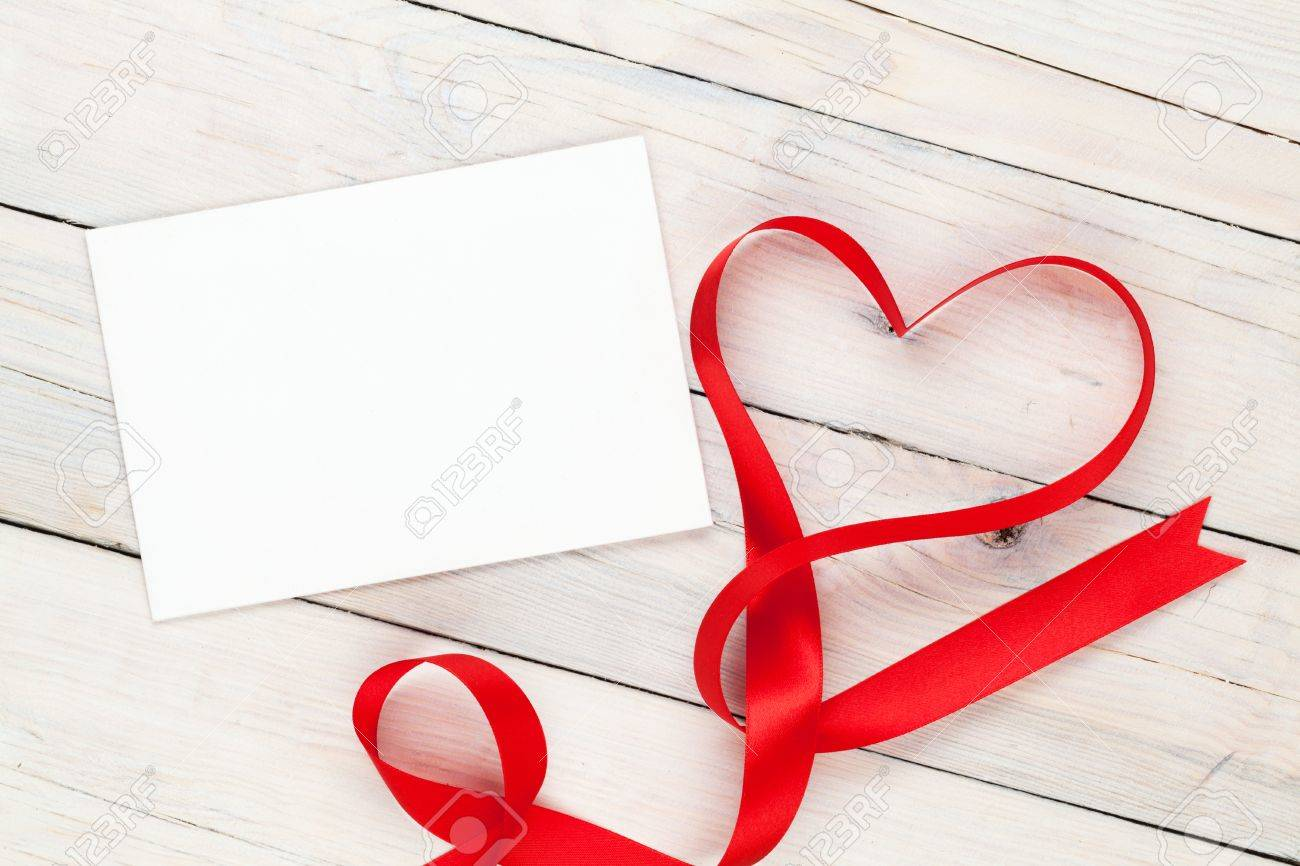 Photo frame or greeting card with valentines heart shaped ribbon photo frame or greeting card with valentines heart shaped ribbon over wooden table background stock photo m4hsunfo