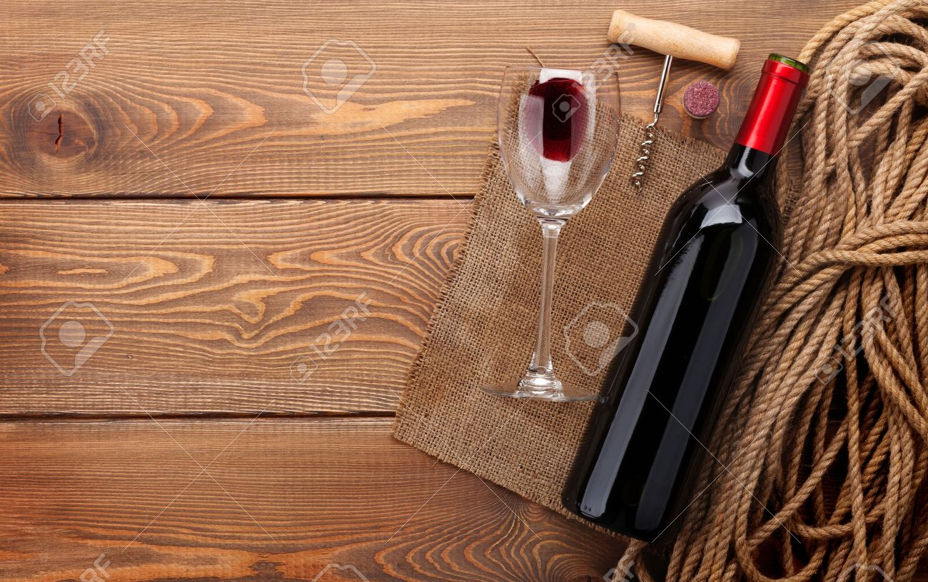 Red Wine Bottle, Wine Glass And Corkscrew On Wooden Table Background With  Copy Space Stock