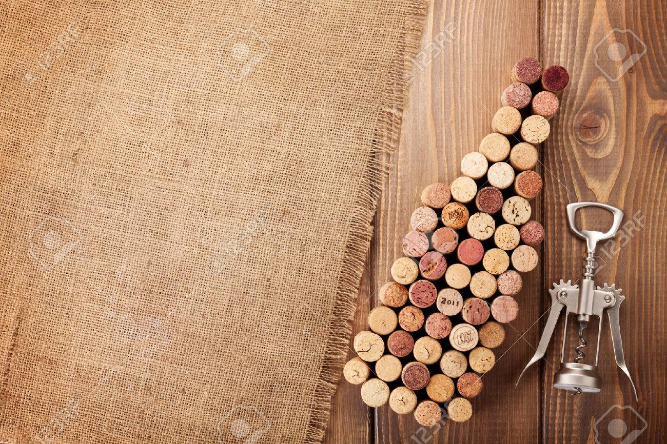 Wine Bottle Shaped Corks And Corkscrew Over Rustic Wooden Table Background  And Burlap. Top View