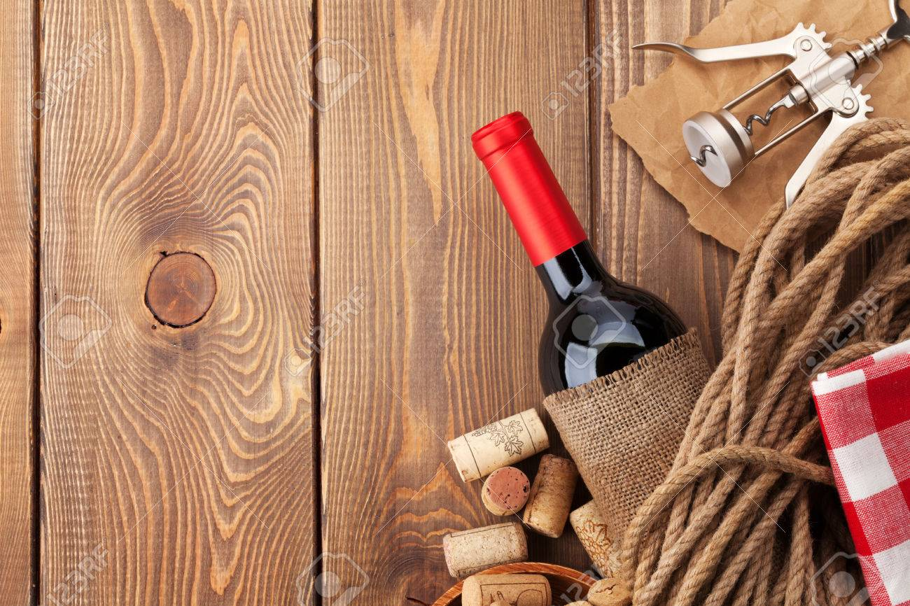 Red Wine Bottle, Corks And Corkscrew Over Wooden Table Background. Top View  With Copy