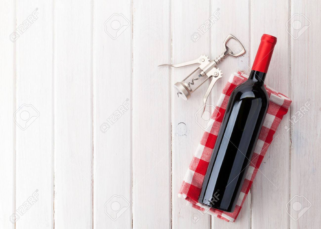 Red Wine Bottle And Corkscrew On White Wooden Table Background With Copy  Space Stock Photo