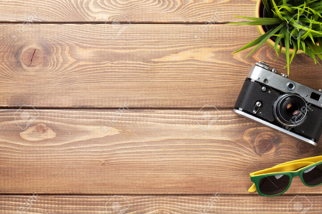 Camera, Sunglasses And Flower On Office Wooden Desk Table. Top ...