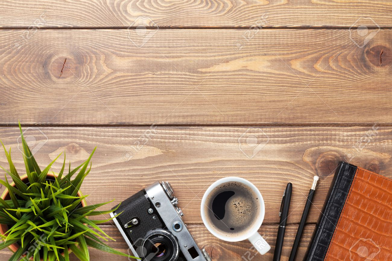 Camera And Supplies On Office Wooden Desk Table Top View With