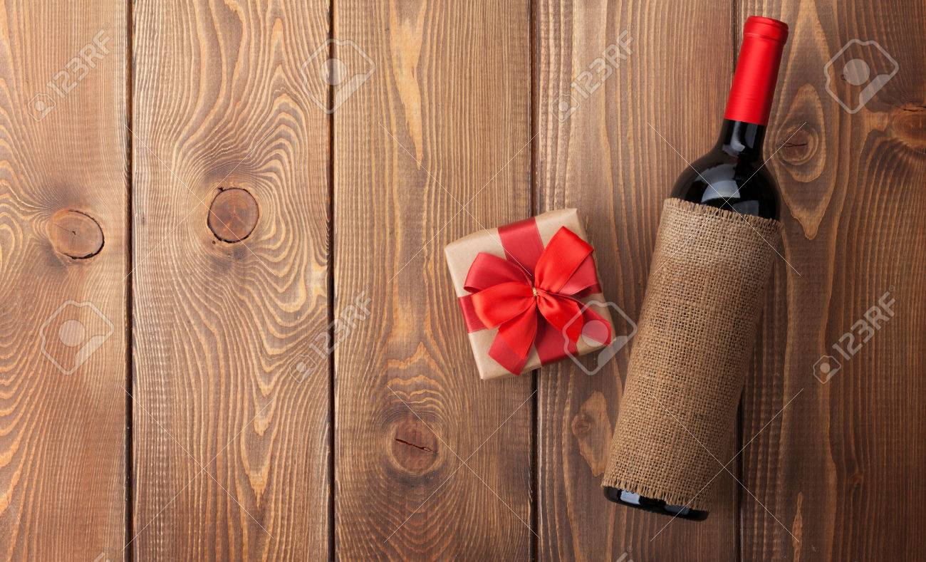 Red Wine Bottle And Valentines Day Gift Box Over Rustic Wooden