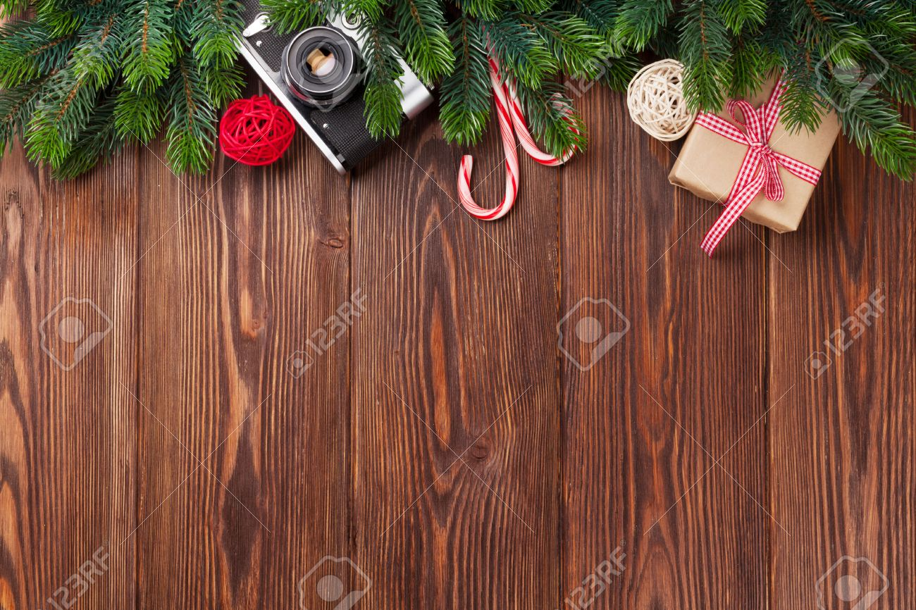 Christmas Tree Branch, Gift Box And Camera On Wooden Table. Top View With  Copy