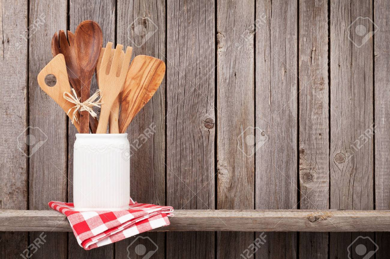 Kitchen Cooking Utensils On Shelf Against Rustic Wooden Wall Stock
