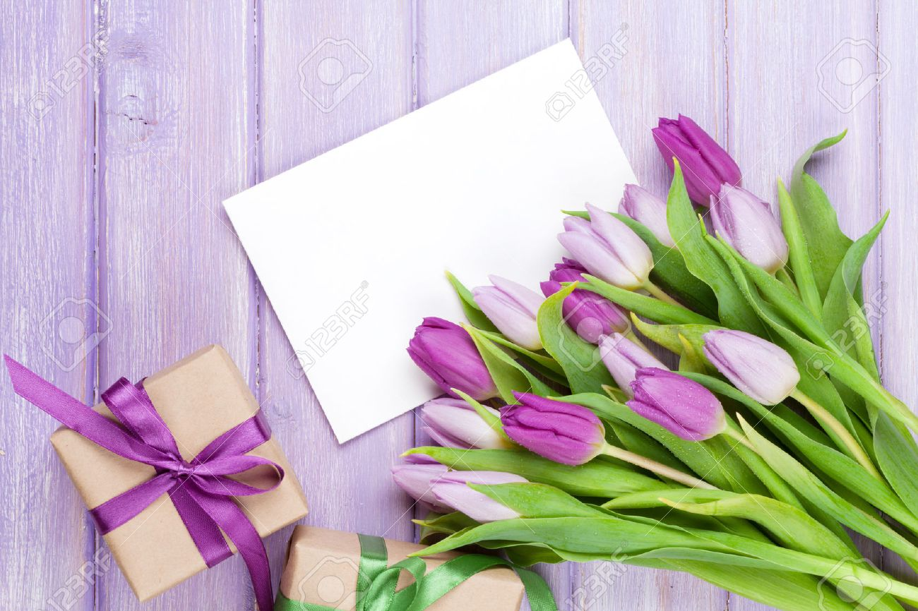 Purple tulip bouquet, blank greeting card and gift boxes. Top view over wooden table - 50679615