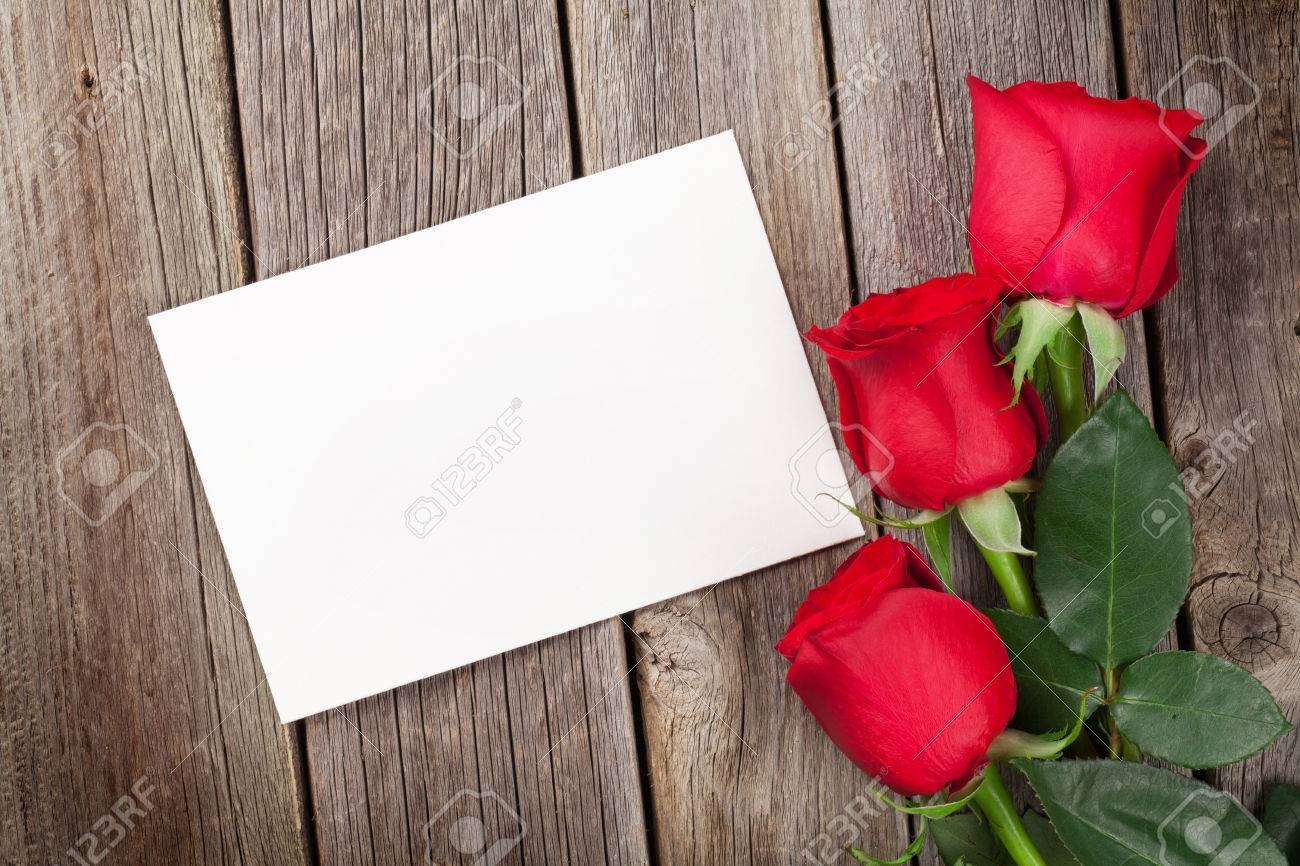 Red Roses And Valentines Day Greeting Card Over Wooden Table