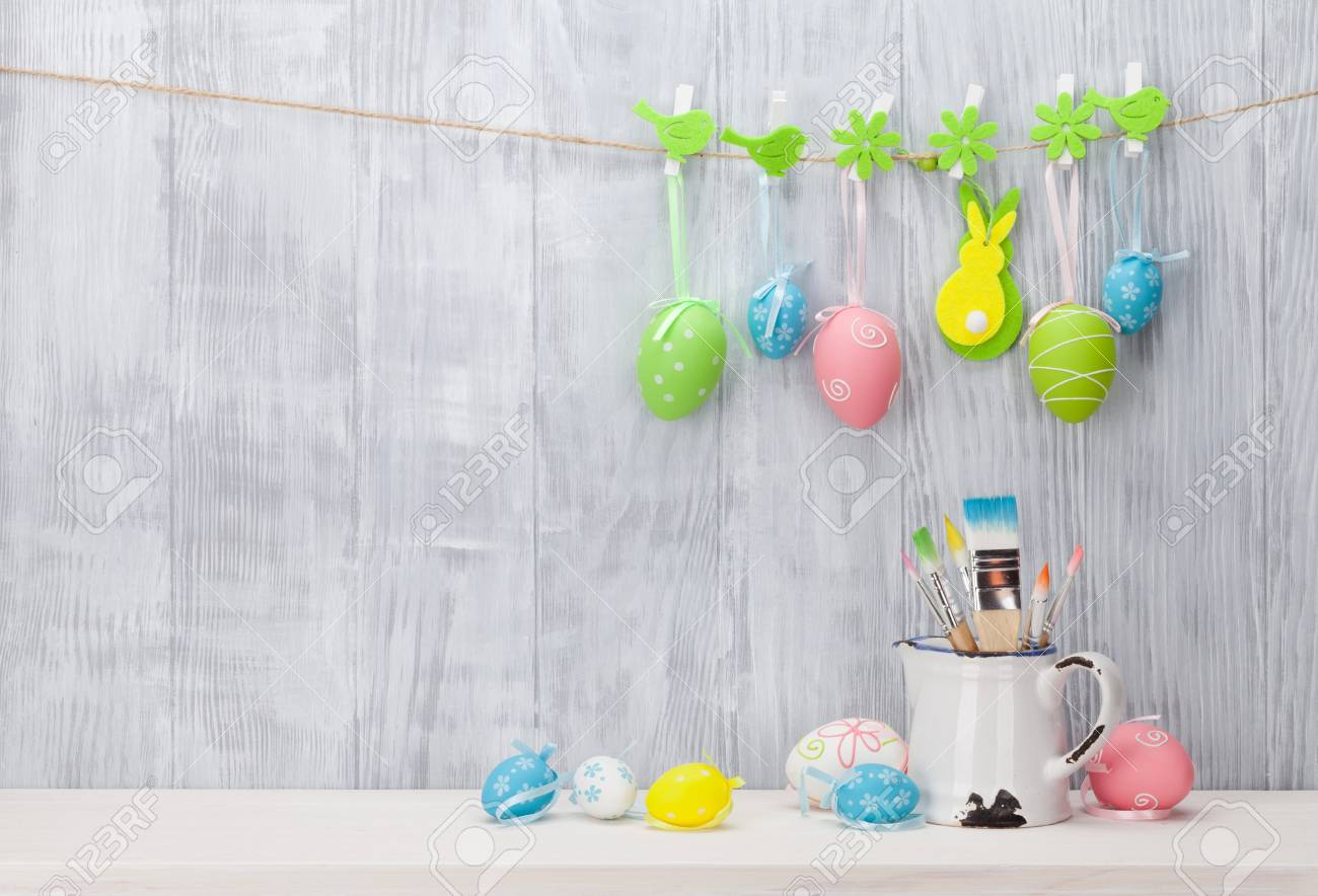 Colorful easter eggs and brushes on shelf in front of wooden wall. View with copy space - 53001150