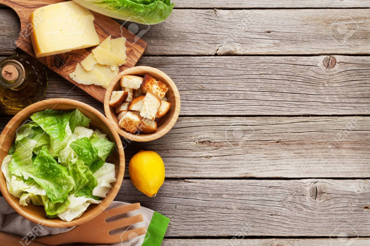 Fresh healthy caesar salad cooking on wooden table. Top view with copy space - 54581798