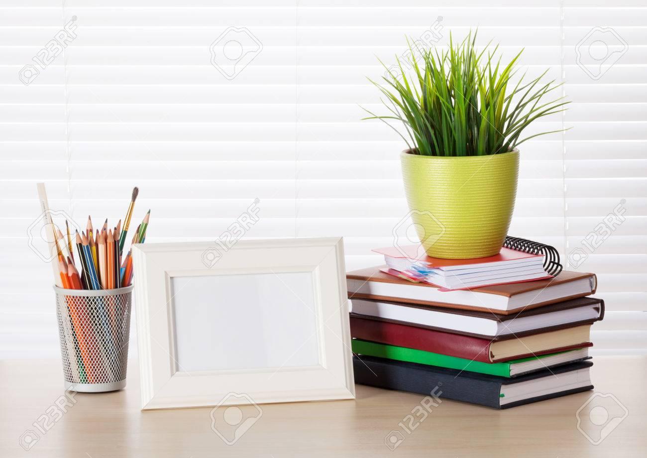 El Lugar De Trabajo De Oficina Con Marco De Fotos, Libros Y Lápices ...