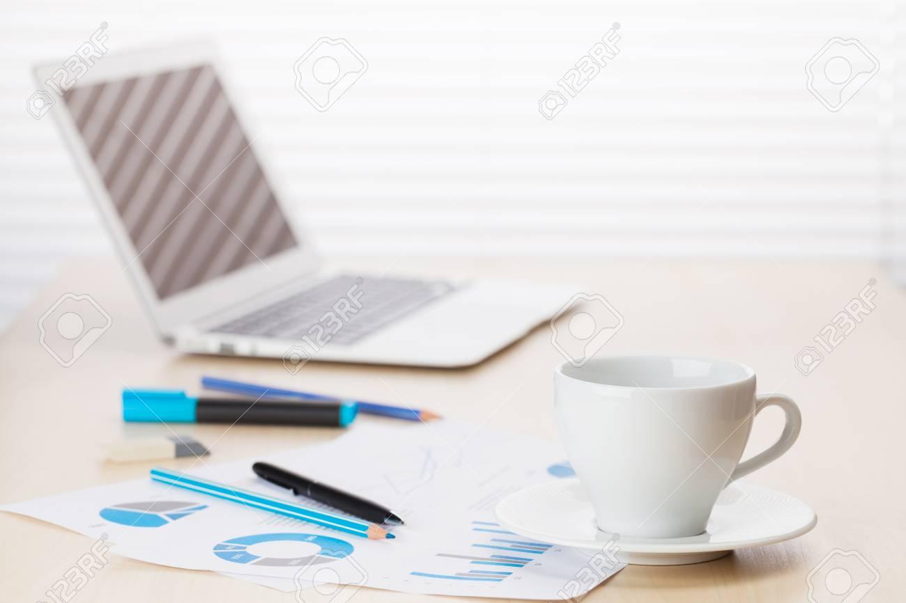 Tavolo Di Ufficio : Posto di lavoro di ufficio con con computer portatile e tazza di