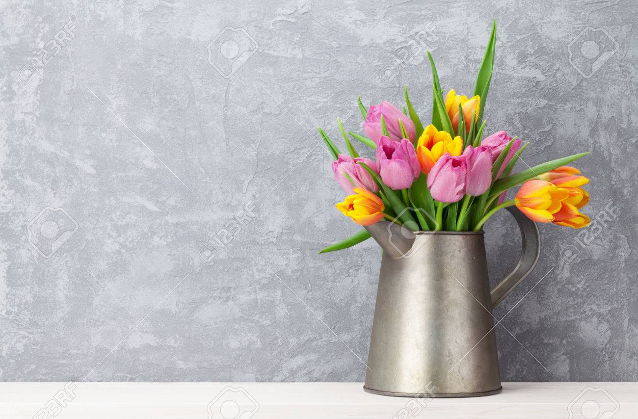 Fresh colorful tulip flowers bouquet in front of stone wall. View with copy space Standard-Bild - 55372757