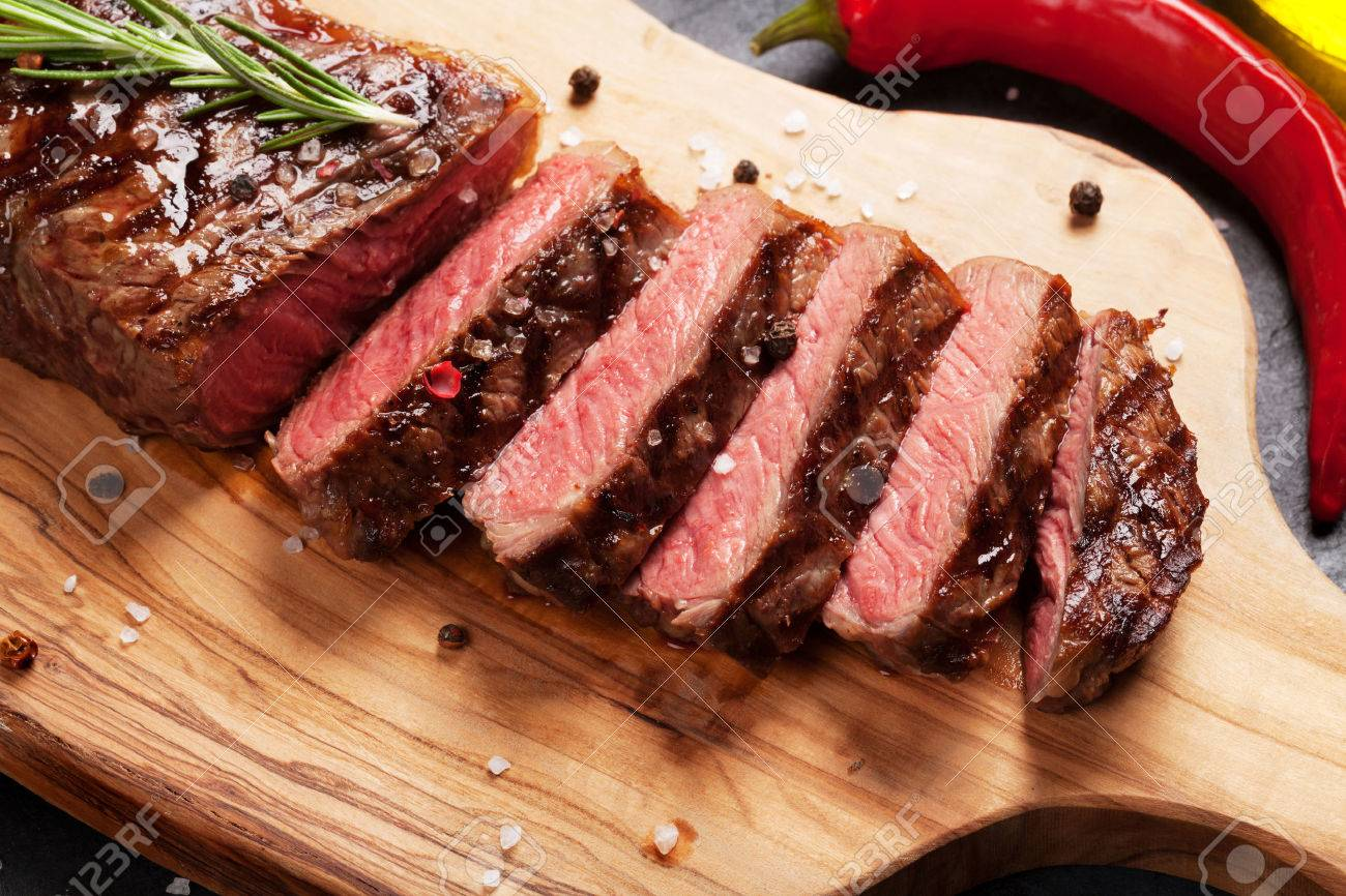 Grilled striploin sliced steak on cutting board over stone table Standard-Bild - 57081529
