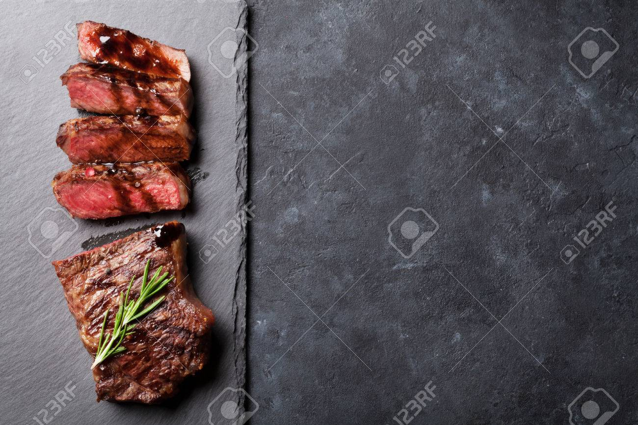 Grilled sliced beef steak with balsamico and rosemary on stone table. Top view with copy space Standard-Bild - 57695614