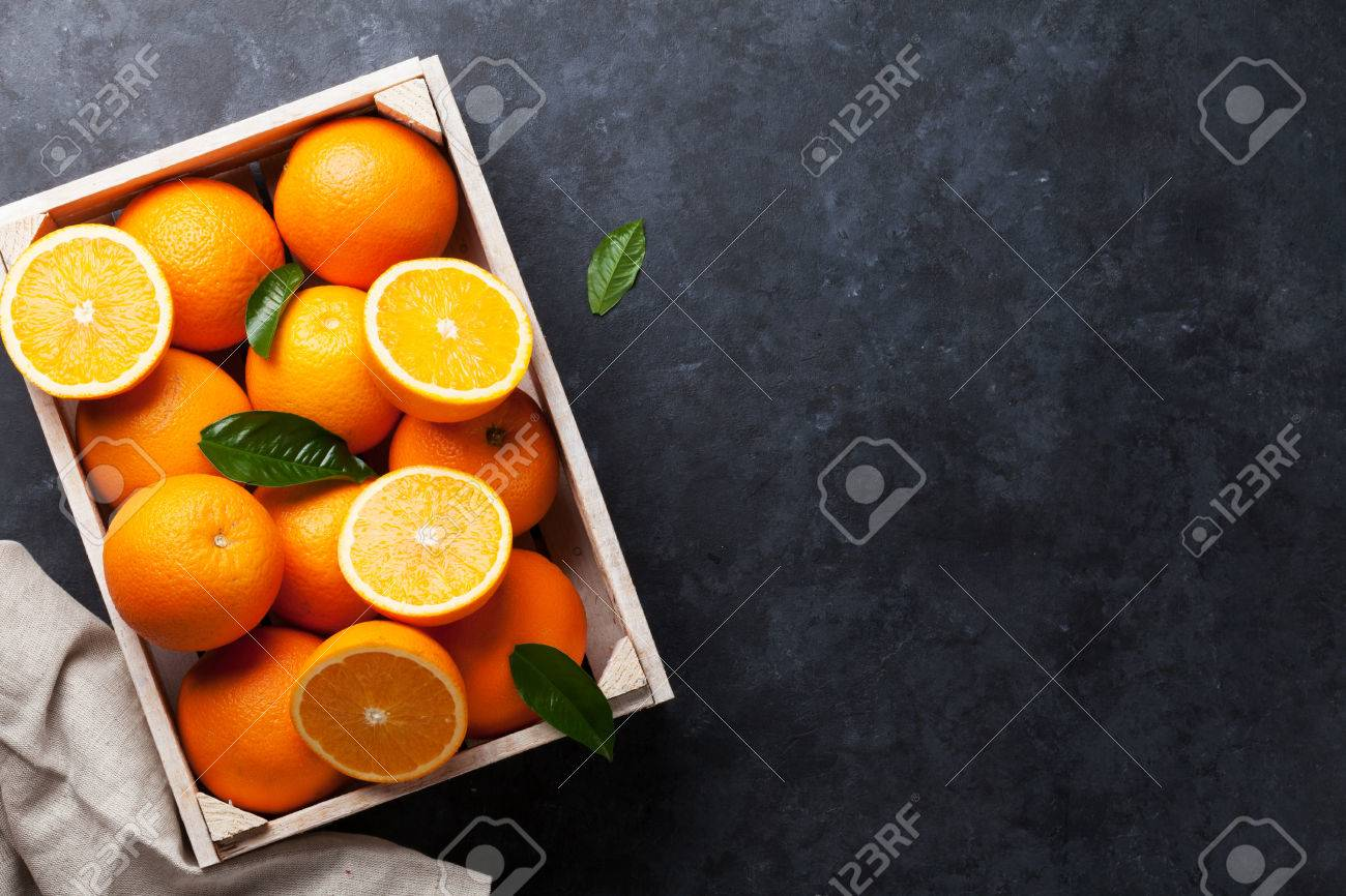 Fresh orange fruits in wooden box on stone table. Top view with copy space Standard-Bild - 57891048