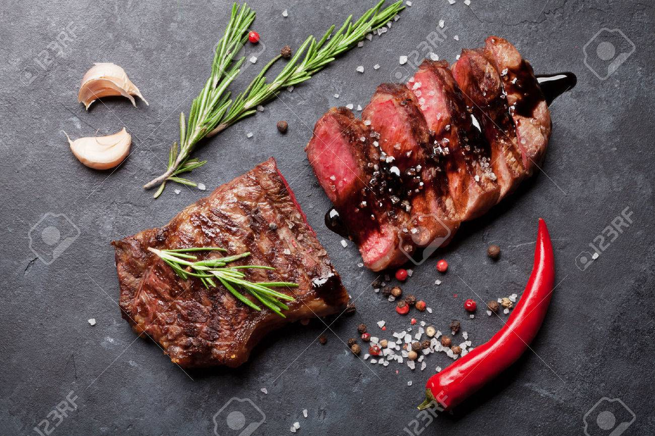 Grilled sliced beef steak with balsamico and rosemary on stone table. Top view Standard-Bild - 57938913