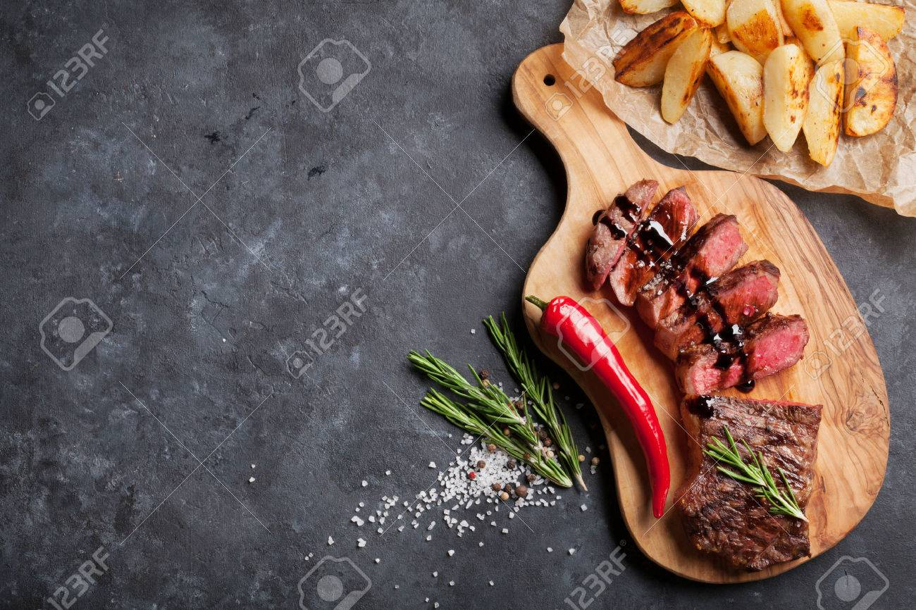 Grilled sliced beef steak on cutting board over stone table. Top view with copy space Standard-Bild - 58503104