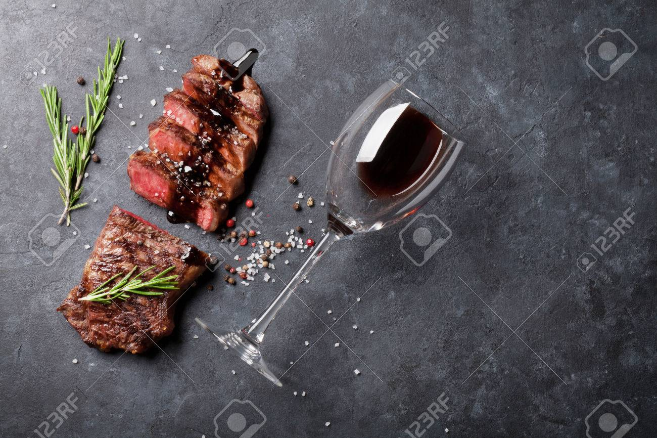 Grilled sliced beef steak with balsamico and rosemary and red wine on stone table. Top view with copy space Standard-Bild - 59182644