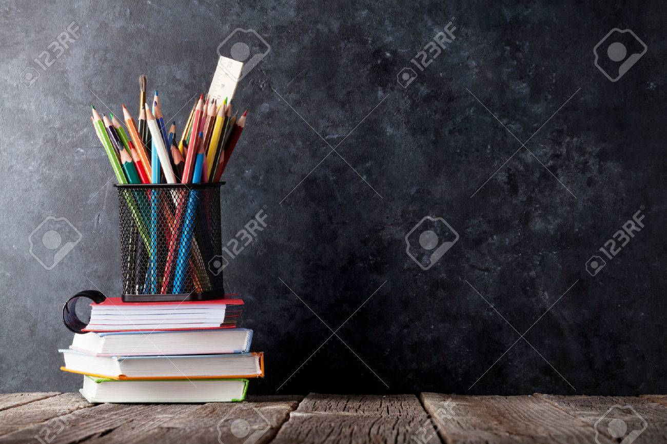 Supplies over notepads in front of chalk board. Back to school concept with copy space Standard-Bild - 60510417