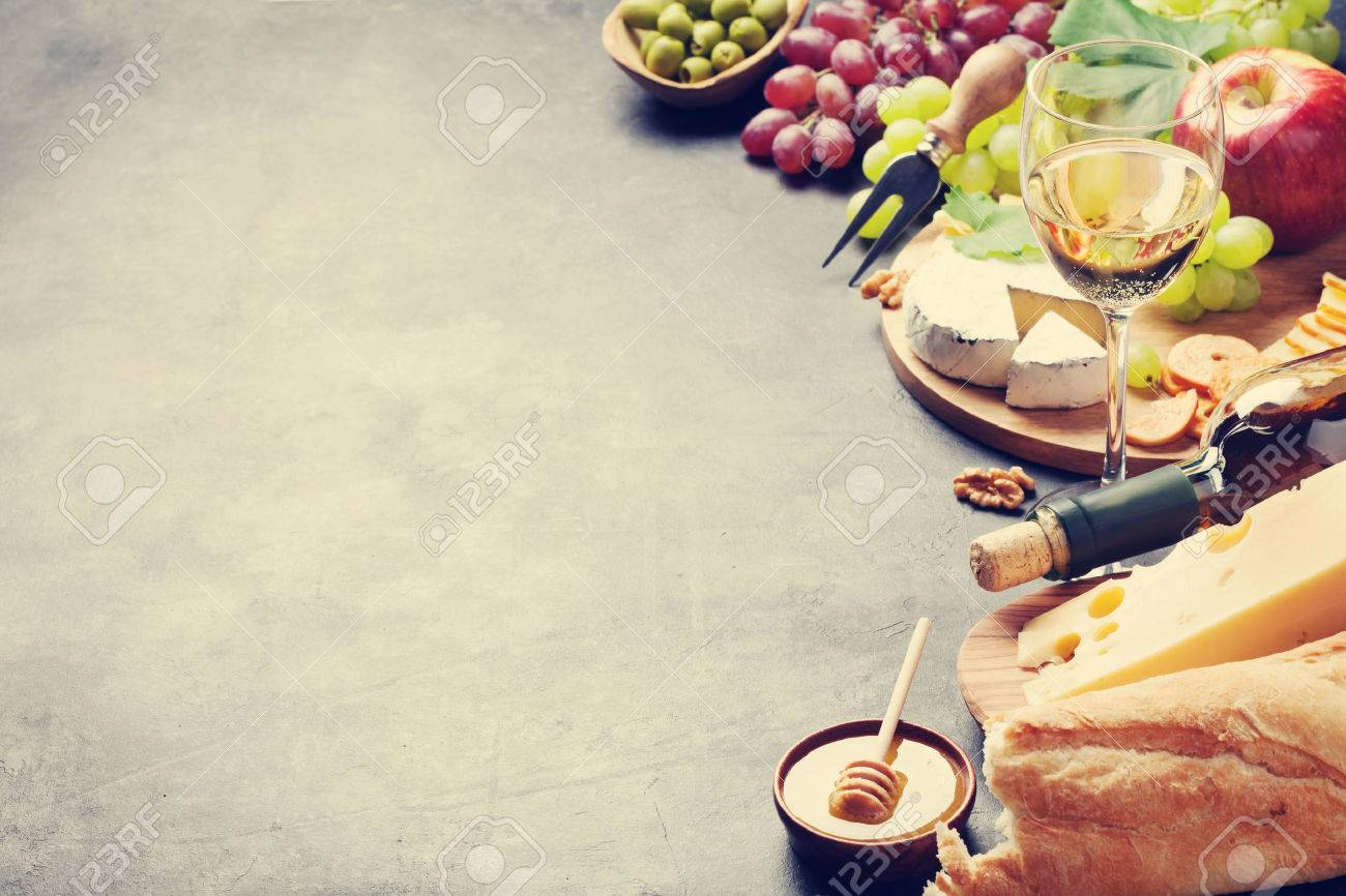 White wine, grape, bread, cheese plate and honey on stone table. View with copy space. Toned Standard-Bild - 61468953