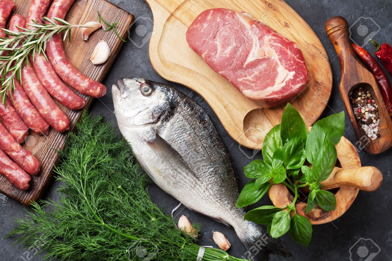 Sausages, fish, meat and ingredients cooking. Top view on stone table Standard-Bild - 62201933