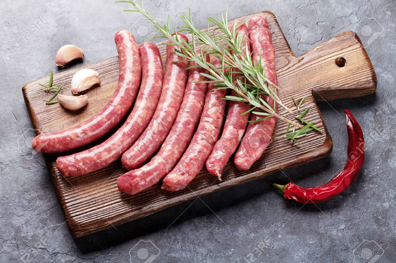Raw sausages and ingredients for cooking on stone table Standard-Bild - 62201689