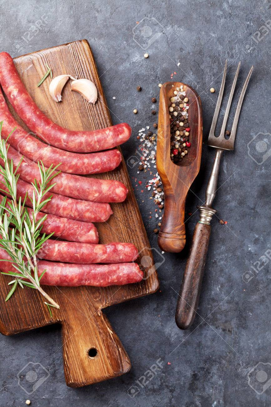 Raw sausages and ingredients for cooking. Top view on stone table - 62473588