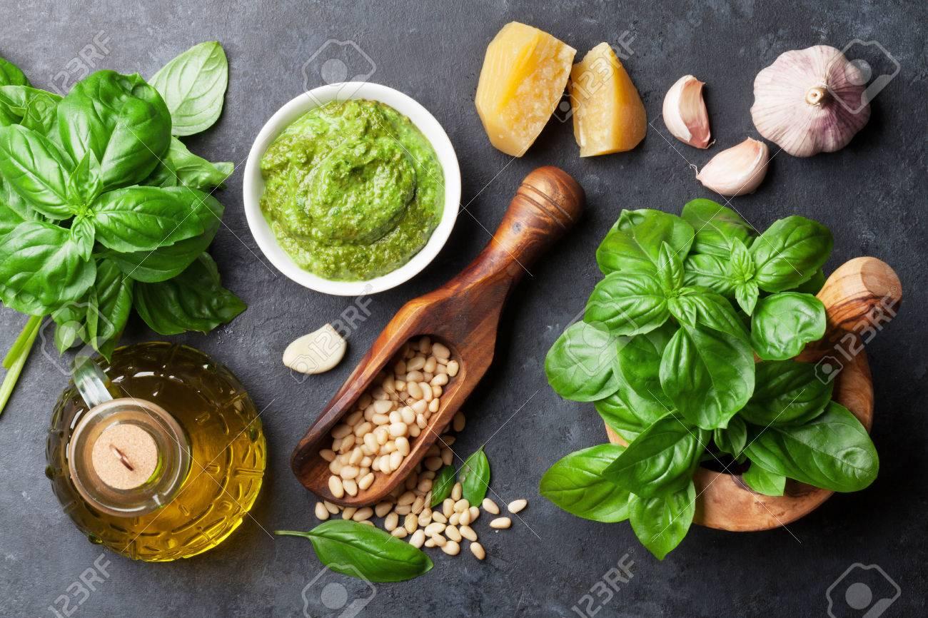 Pesto sauce cooking. Basil, olive oil, parmesan, garlic, pine nuts. Top view on dark stone table - 62473533