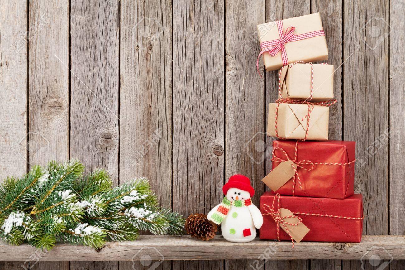 Sapin De Noel Sur Le Mur coffrets-cadeaux de noël et branche de sapin devant un mur en bois avec  espace copie