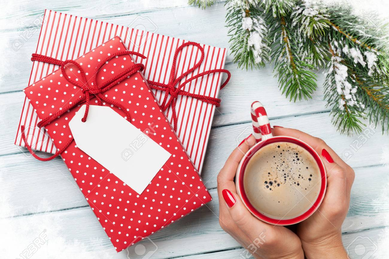 Female Hands Holding Coffee Cup, Christmas Gift Boxes And Snow ...