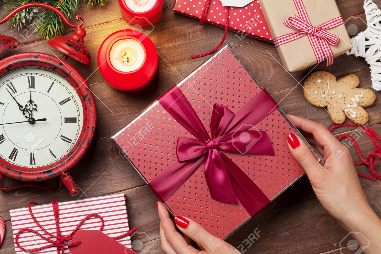Female hands holding christmas gift above wooden table top view female hands holding christmas gift above wooden table top view xmas gift wrapping stock negle Images