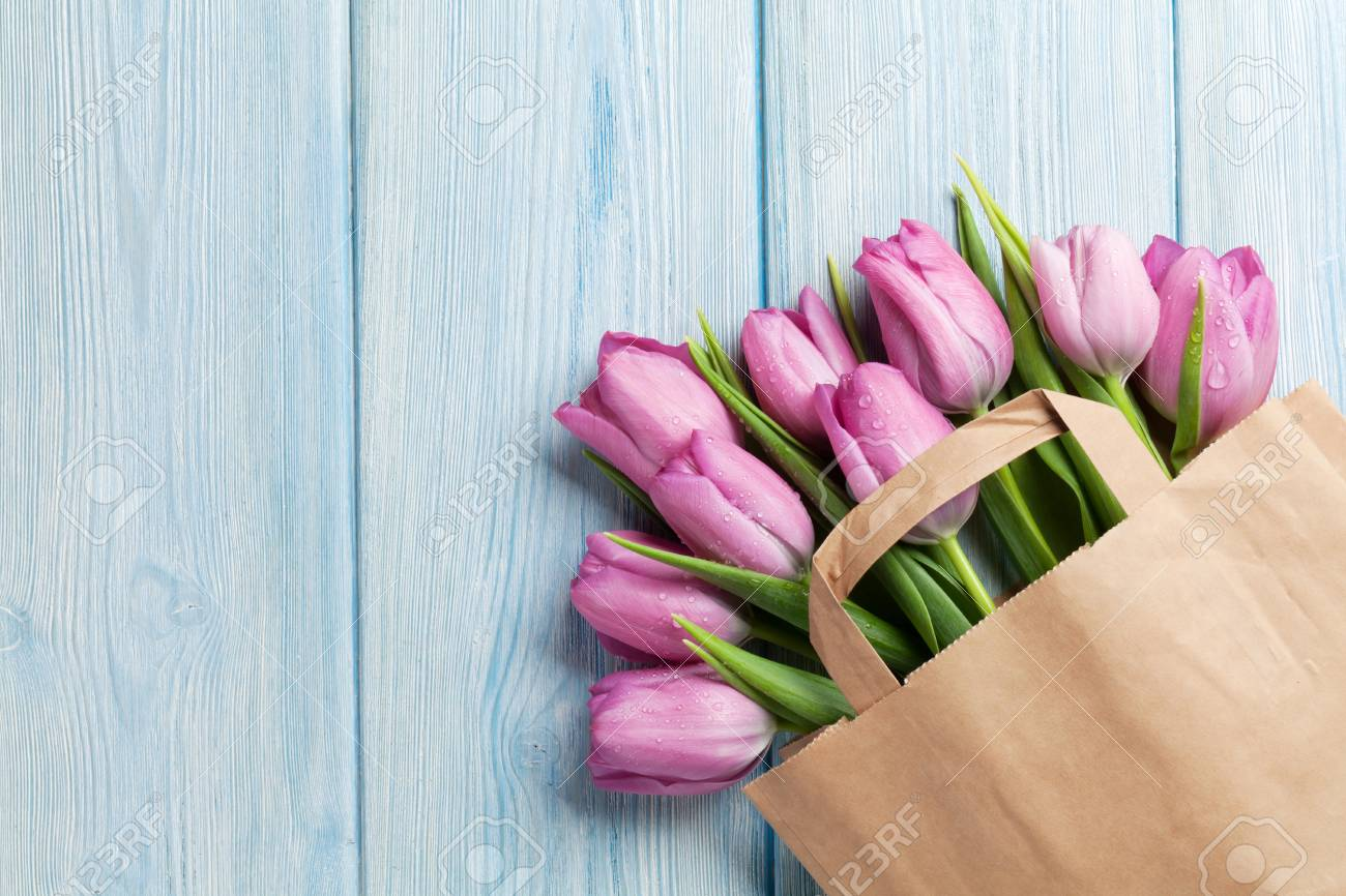 Fresh Pink Tulip Flowers In Paper Bag On Wooden Table Top View