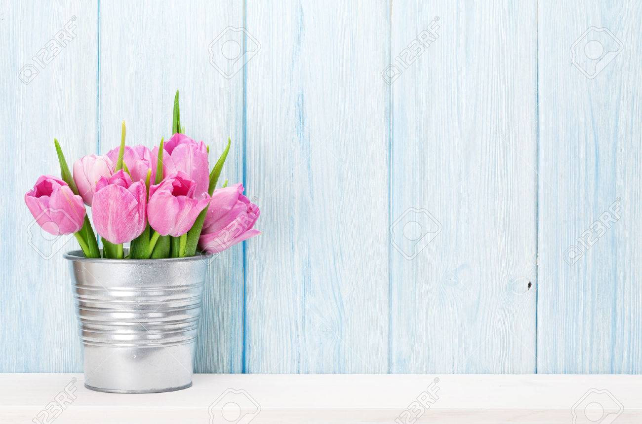 Fresh pink tulip flowers bouquet on shelf in front of wooden wall. View with copy space Standard-Bild - 69595054