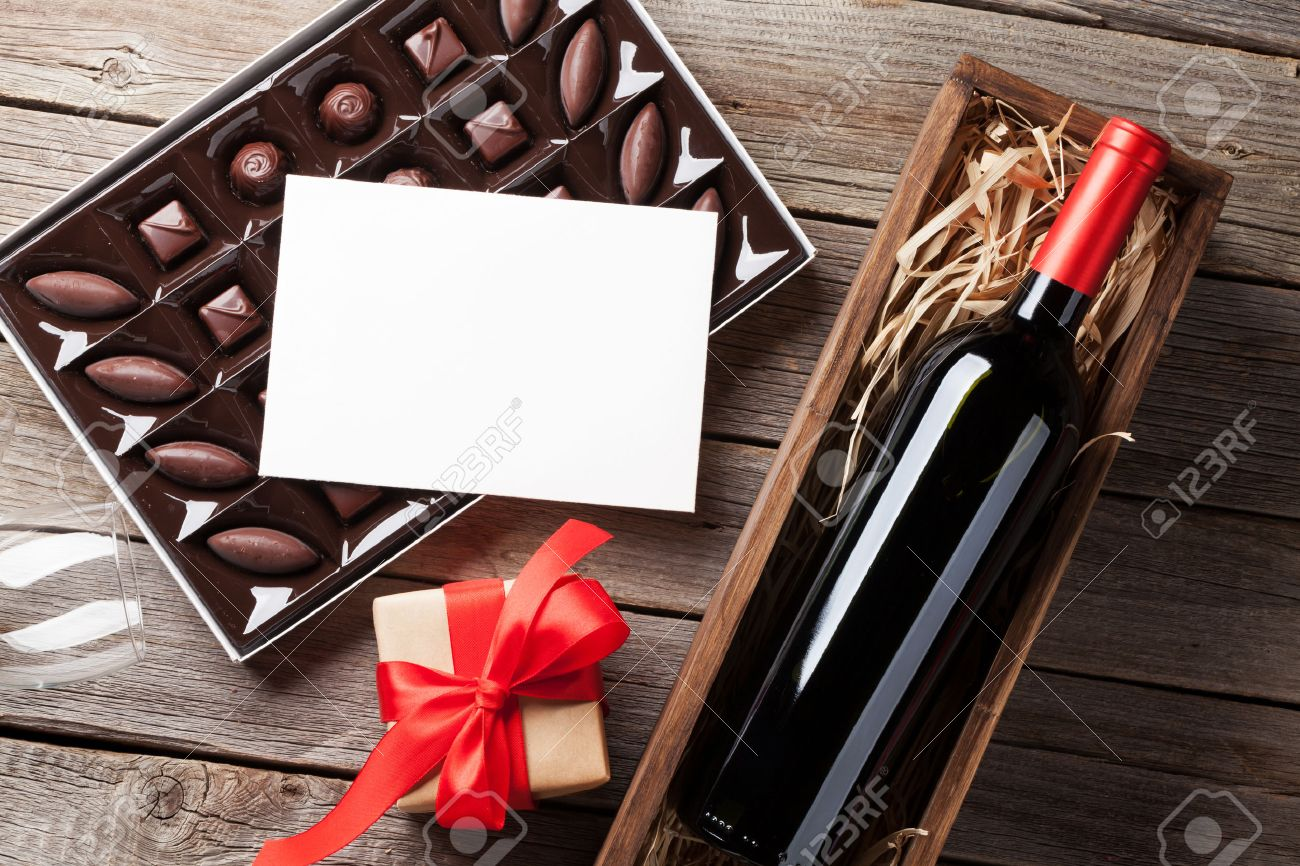 Valentines day greeting card. Red wine, gift box and chocolate box on wooden table. Top view with space for greetings Standard-Bild - 69949290