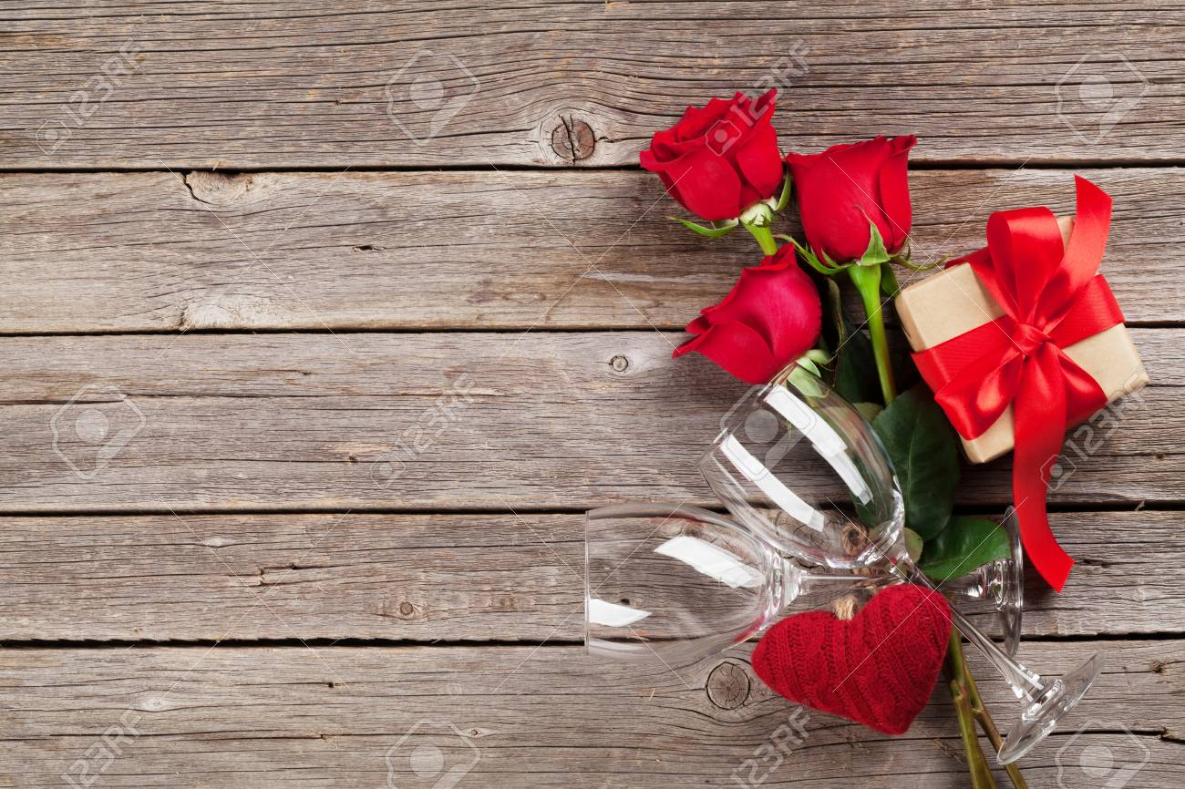 Valentines day greeting card red roses heart and gift box on valentines day greeting card red roses heart and gift box on wooden table kristyandbryce Choice Image