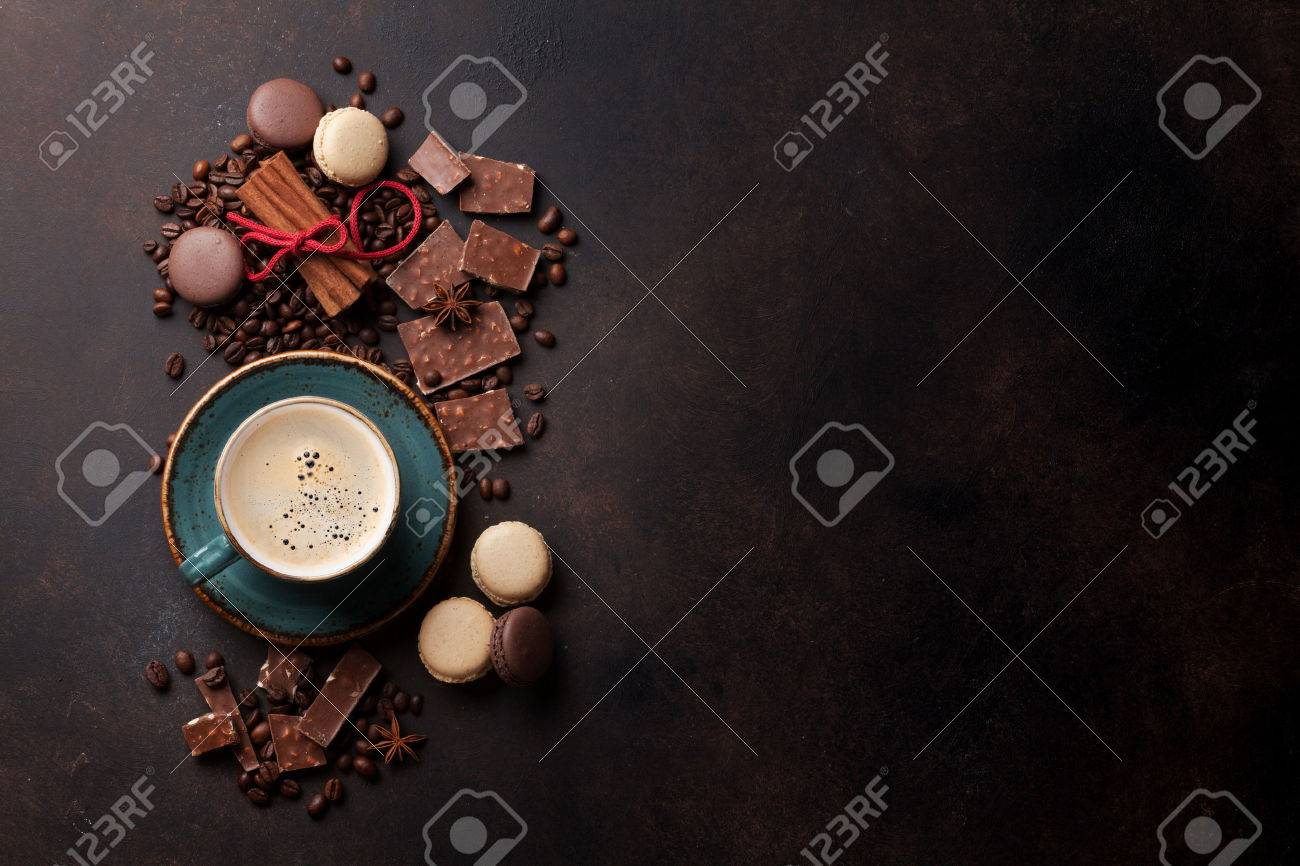 Coffee cup, beans, chocolate and macaroons on old kitchen table. Top view with copyspace for your text Standard-Bild - 72122515