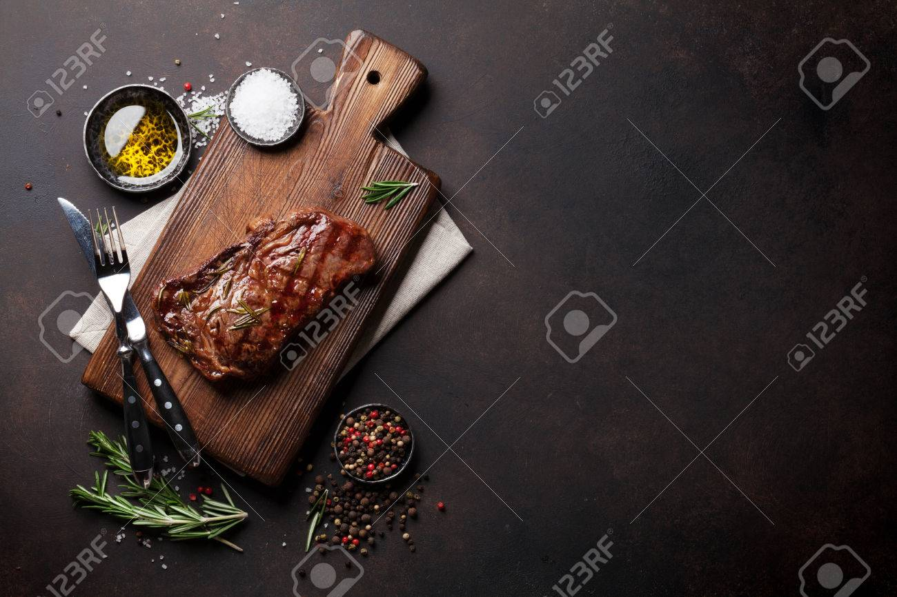 Grilled ribeye beef steak, herbs and spices. Top view with copy space for your text Standard-Bild - 72526102