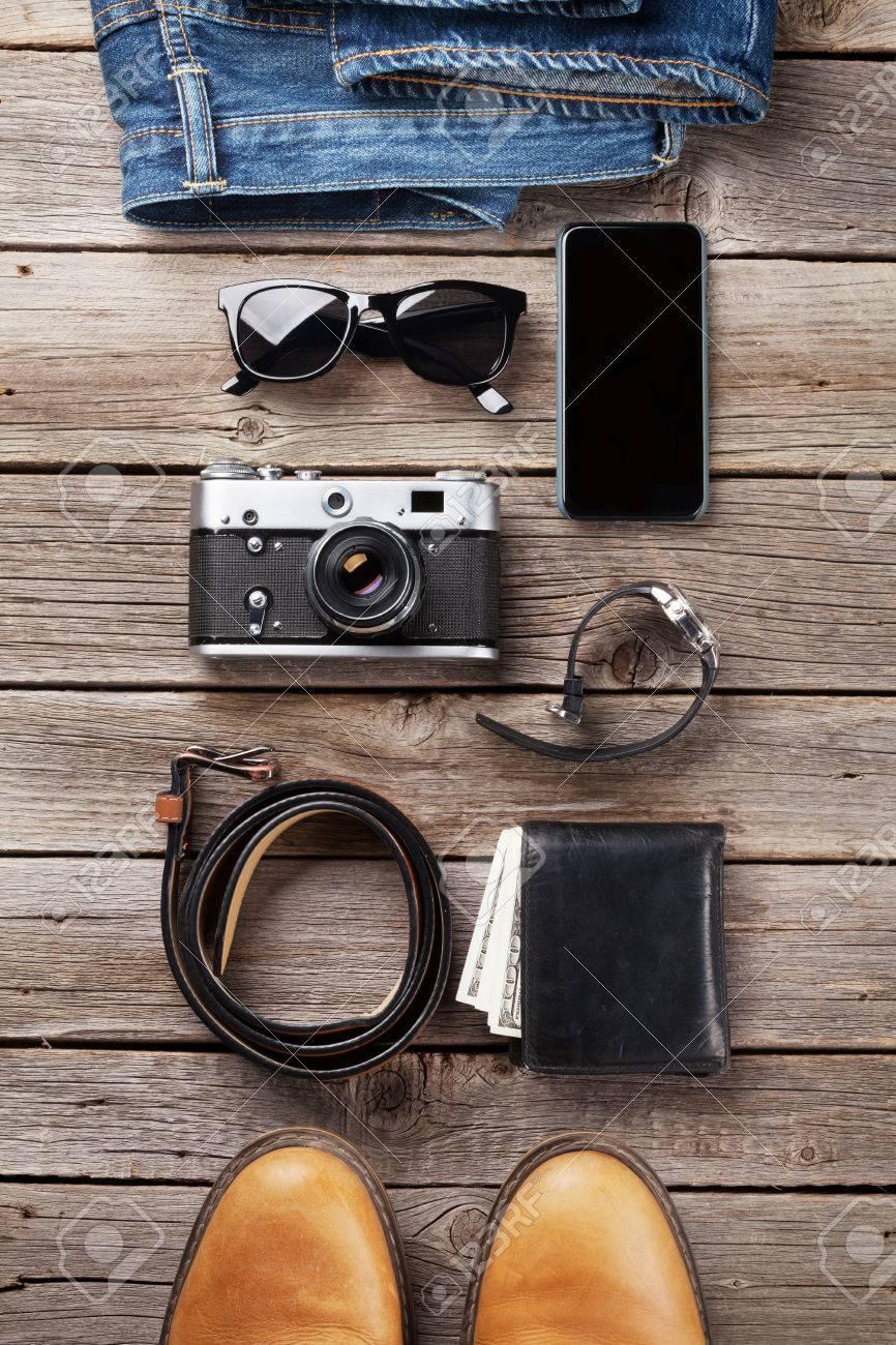 Ropa y accesorios para hombres. Jeans, zapatos, gafas, cámara, teléfono inteligente en el fondo de madera. Vista superior