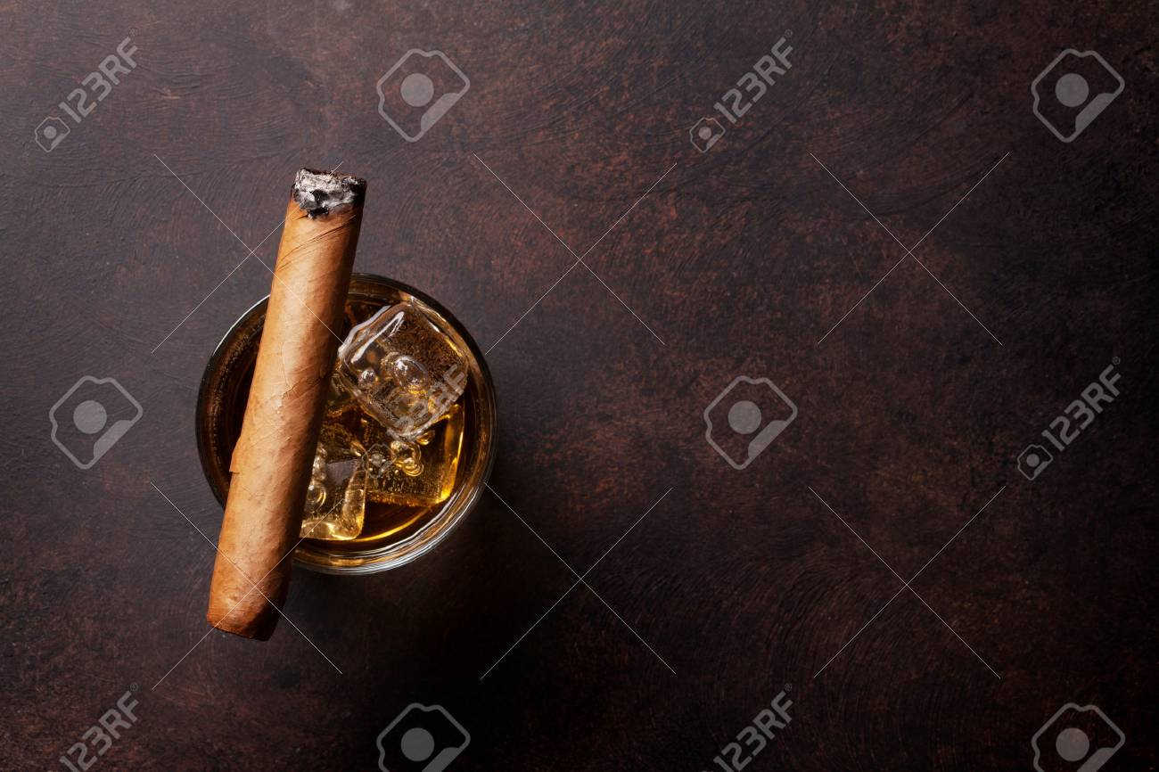 Whiskey with ice and cigar. Top view with copy space - 80475765