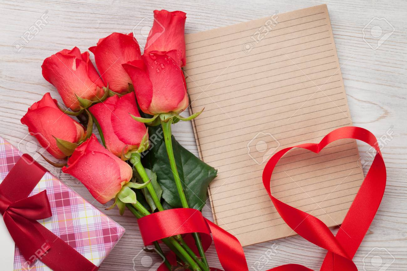 Valentines day greeting card with red roses and heart shaped stock stock photo valentines day greeting card with red roses and heart shaped ribbon on wooden background top view with space for your greeting m4hsunfo
