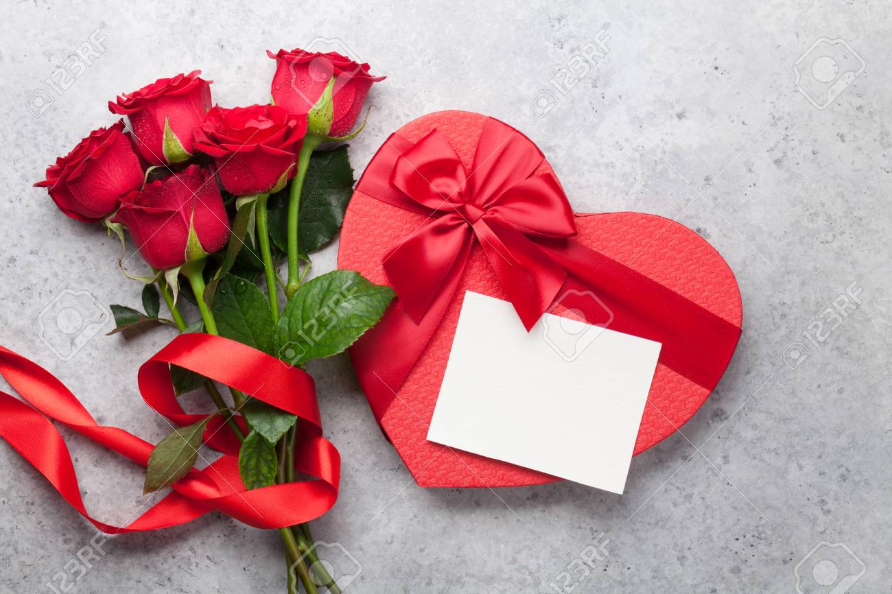 Valentine's day greeting card with red rose flowers bouquet and gift box on stone background. Top view with space for your greetings - 114733567